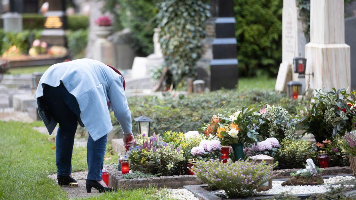 Symbolbild Allerheiligen: Frau zündet Kerze auf dem Salzburger Kommunalfriedhof an