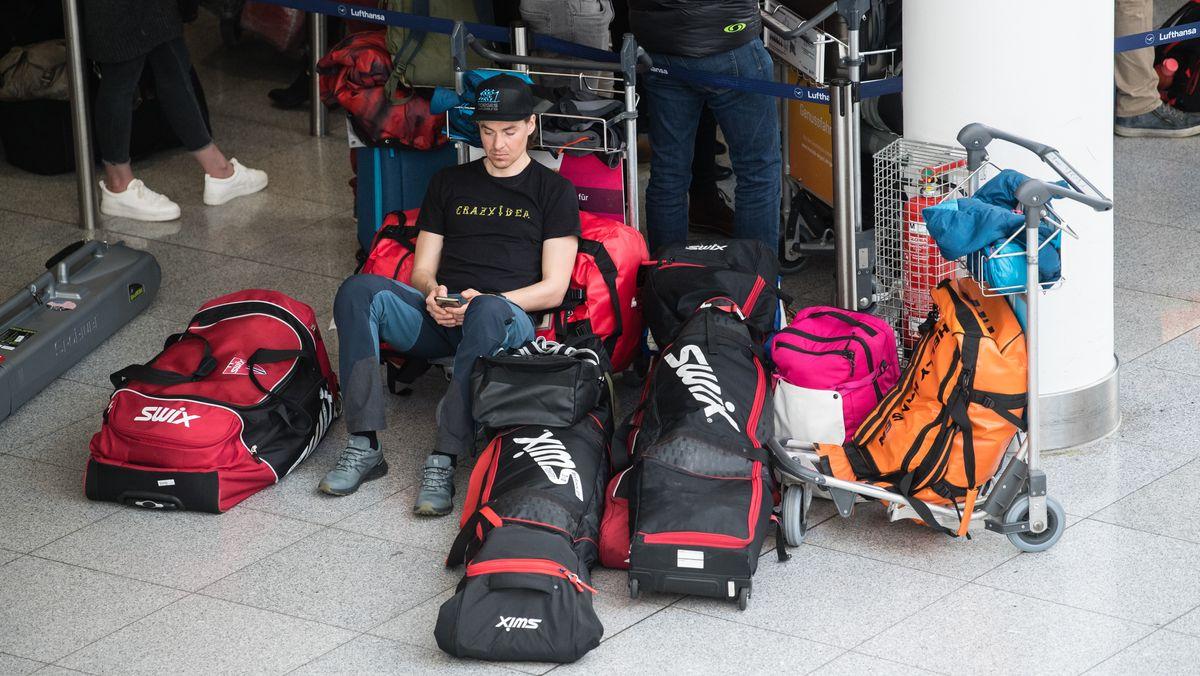 Oie aus Norwegen sitzt umgeben von zahlreichen Gepäckstücken im Terminal des Münchner Flughafens.