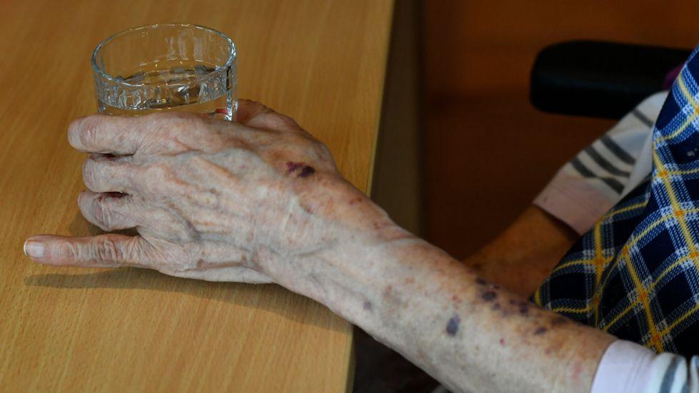 ARCHIV - 10.05.2019, Berlin: Eine alte Frau greift nach einem Glas Wasser.