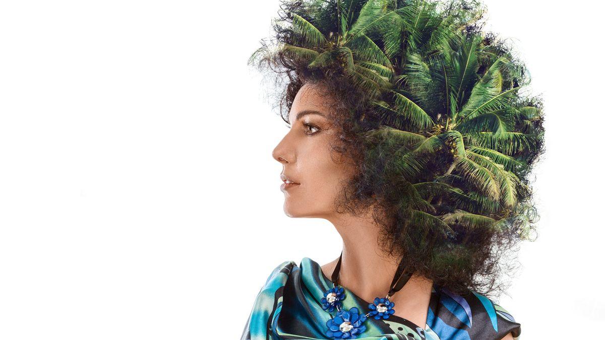 Eine Frau, auf deren Kopf statt Haaren Palmen wachsen.