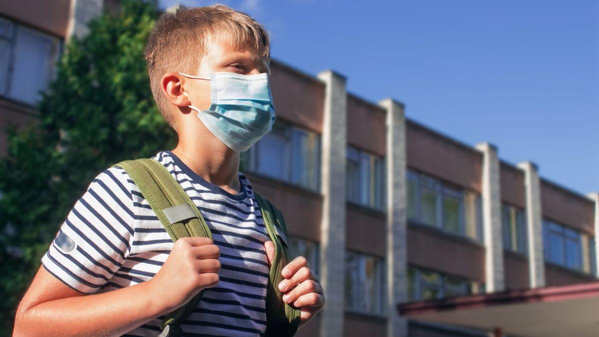 Junge mit Mund-Nasen-Maske vor einer Schule (Symbolbild)