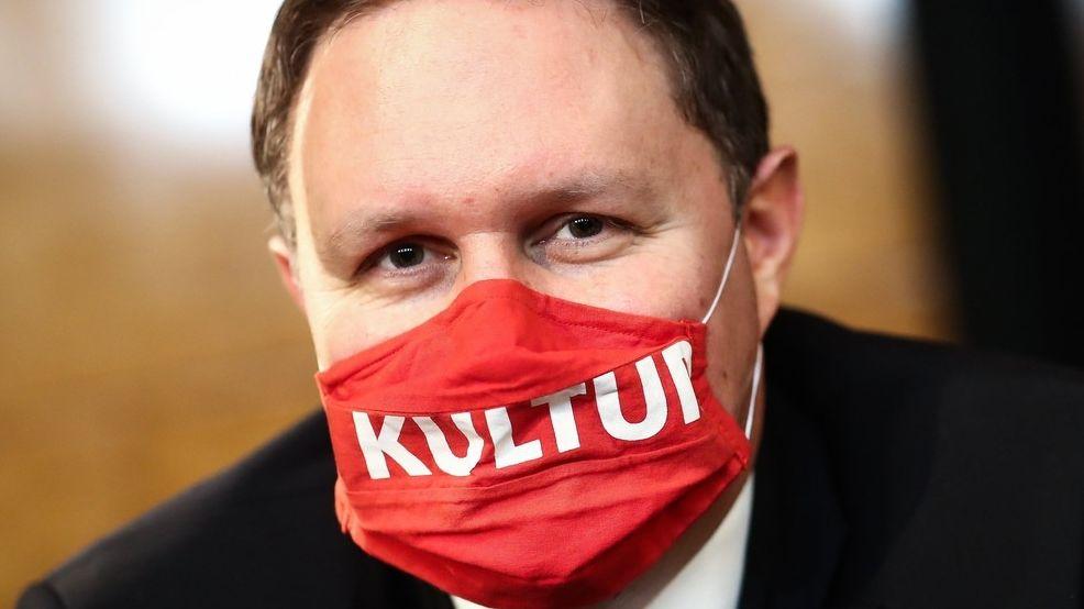 """Carsten Brosda trägt einen roten Mundschutz, auf dem in großen, weissen Lettern """"Kultur"""" steht."""