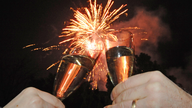 Ein Paar stößt vor einem Feuerwerk mit Sekt auf das Neue Jahr an.