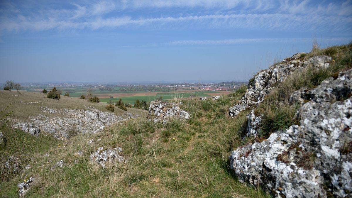 Hinter schroffen Felsen liegt der flache Rieskrater. Dahinter die Stadt Nördlingen.