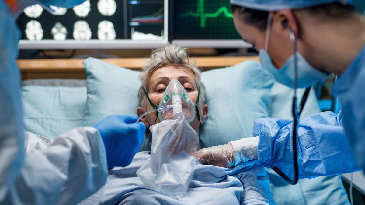 Eine Patientin mit Atemmaske wird im Krankenhaus von Ärzten versorgt.