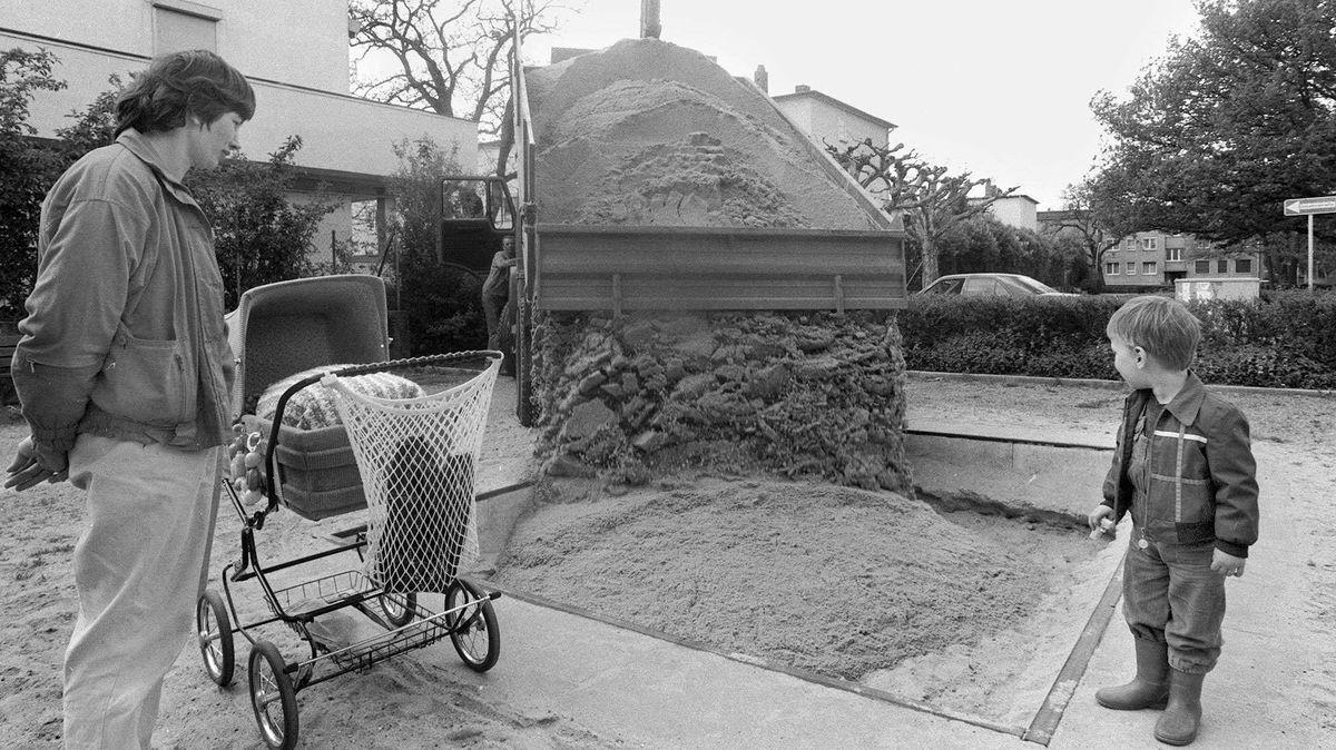 Schwarz-Weiß-Bild vom Frühling 1986: Ein Lastwagen lässt eine Fuhre neuen Sand in einen Sandkasten. Ein Erwachsener mit Kinderwagen und ein Kleinkind schauen zu.