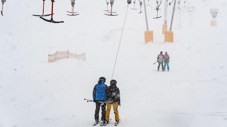 Sankt Englmar: Wintersportler fahren am Predigtstuhl mit einem Skilift im Schneegestöber.