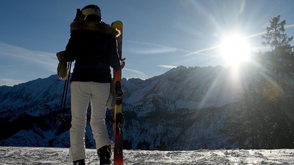 Garmisch-Partenkirchen: Eine Skifahrerin trägt bei Sonnenschein ihre Ski. | Bild:dpa/Angelika Warmuth