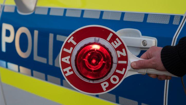 """Ein """"Halt Polizei"""" Schild in der Hand eines Polizisten."""