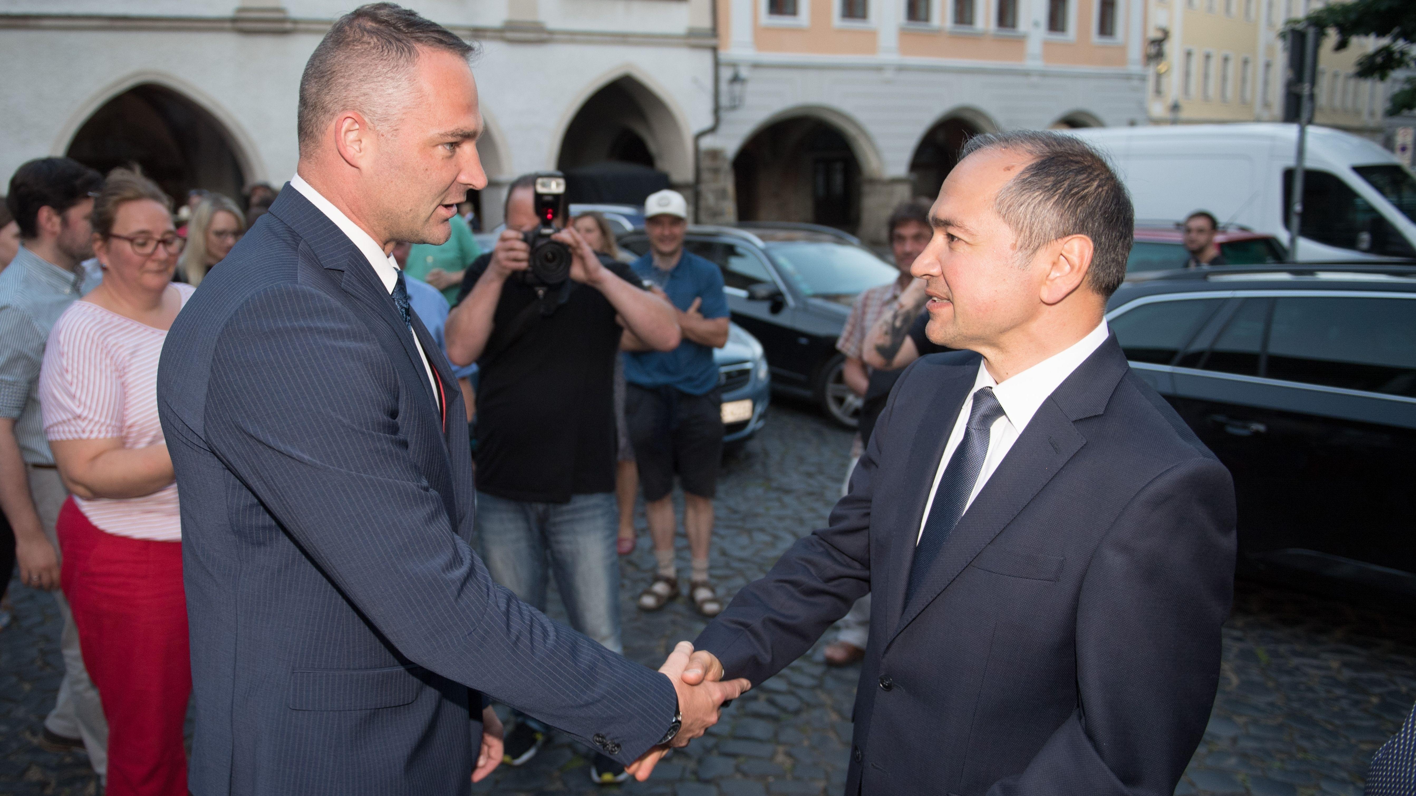 Sebastian Wippel (l), AfD-Landtagsabgeordneter und Oberbürgermeisterkandidat für Görlitz, gratuliert Octavian Ursu (CDU), Oberbürgermeisterkandidat für Görlitz, auf dem Untermarkt.