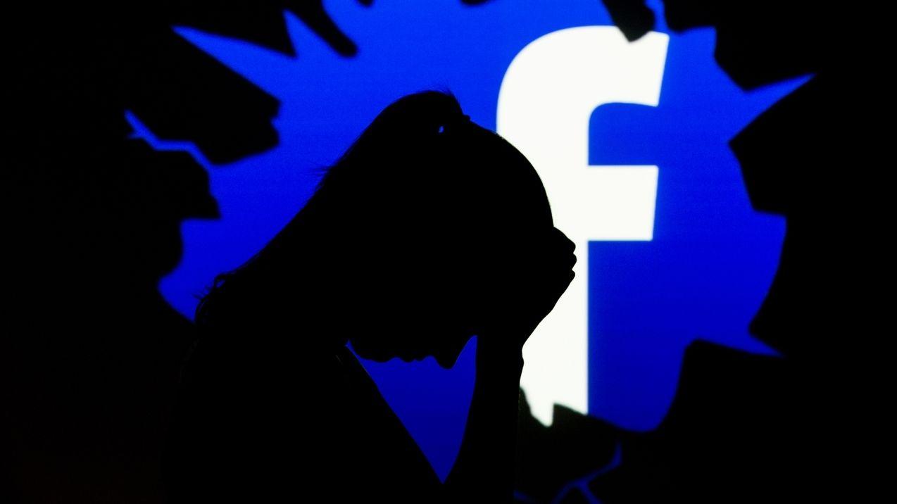 Die Silhouette einer traurigen Frau ist vor dem Symbol des Sozialen Netzwerks Facebook zu sehen.