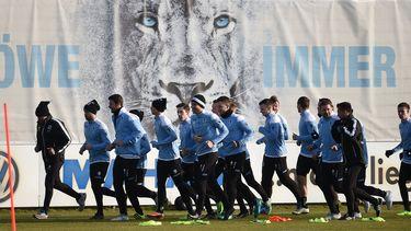 Spieler vom TSV 1860 München laufen sich bei einem Training auf dem Vereinsgelände warm.