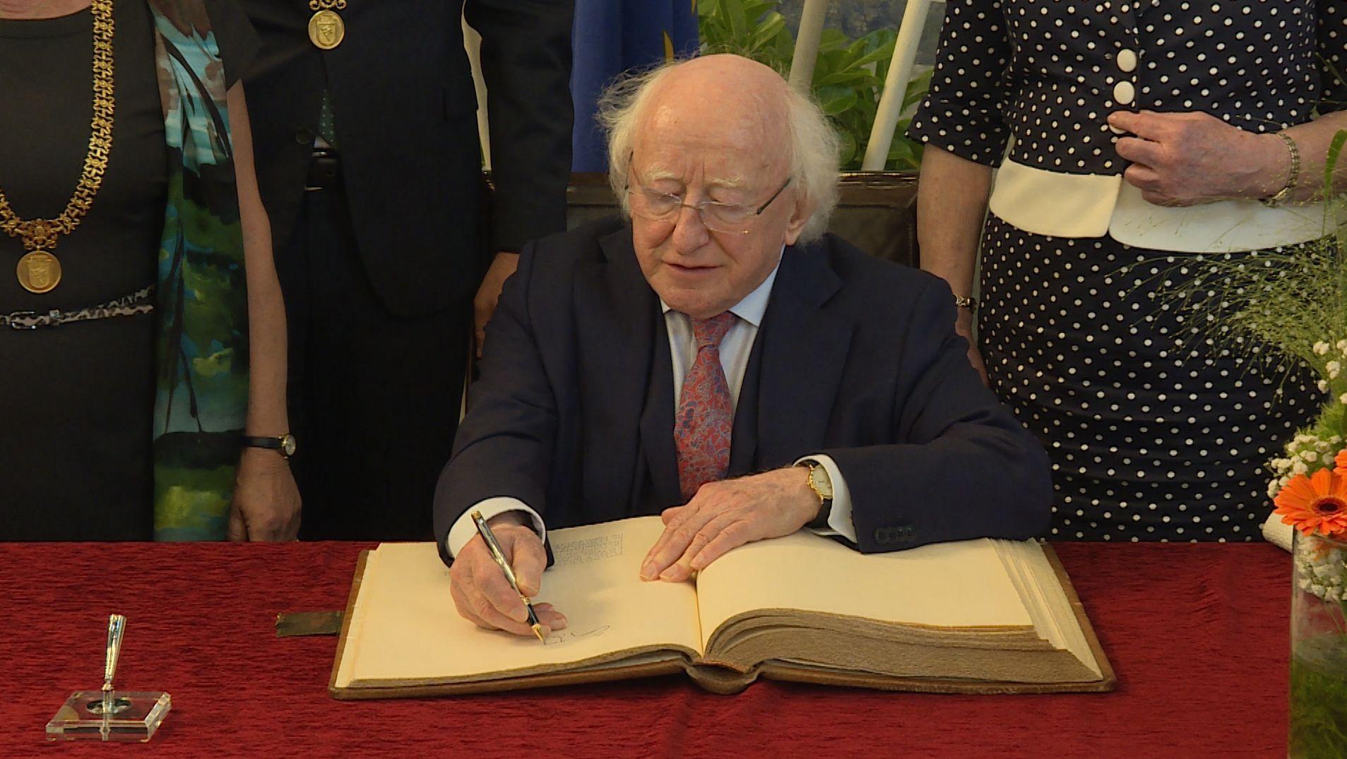 Staatspräsident Michael D. Higgins trägt sich ins Goldene Buch der Stadt Würzburg ein.