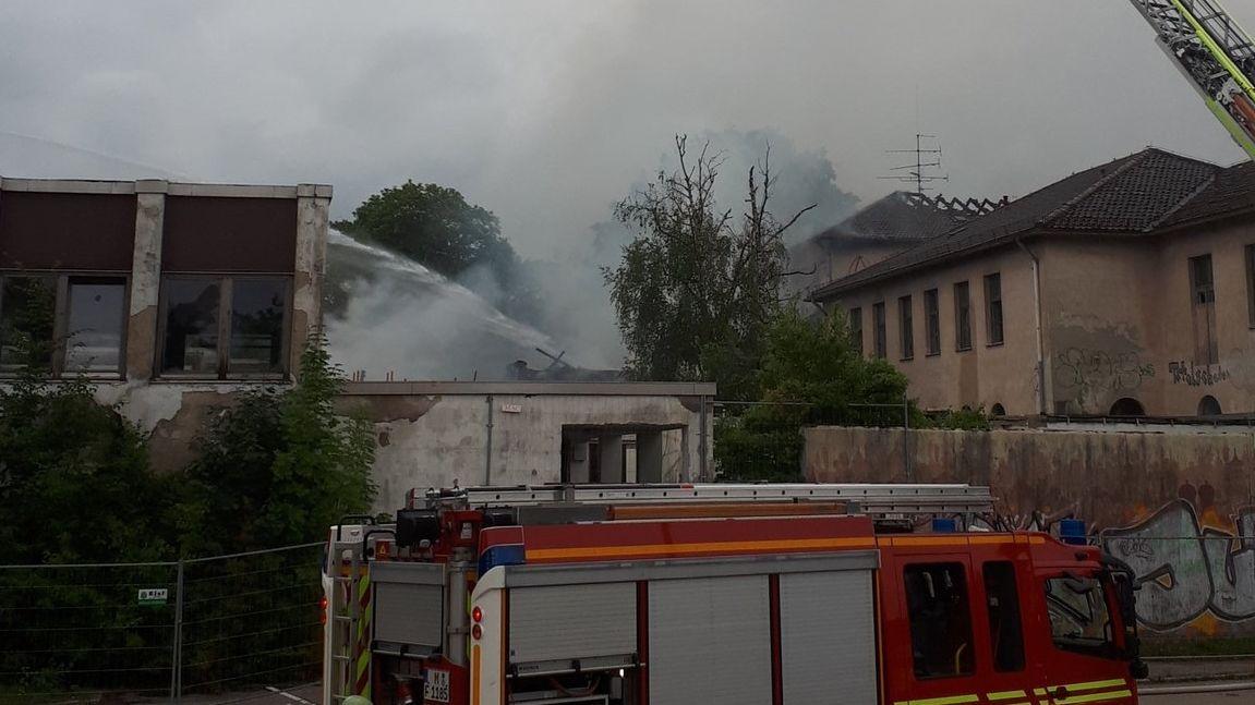 Ein Löschfahrzeug der Feuerwehr vor brennenden Gebäuden.