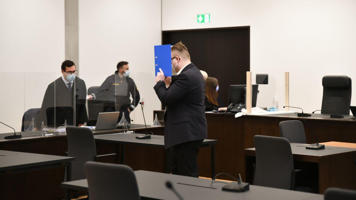 Mann in einem Gerichtssaal hält sich blauen Ordner vor das Gesicht.