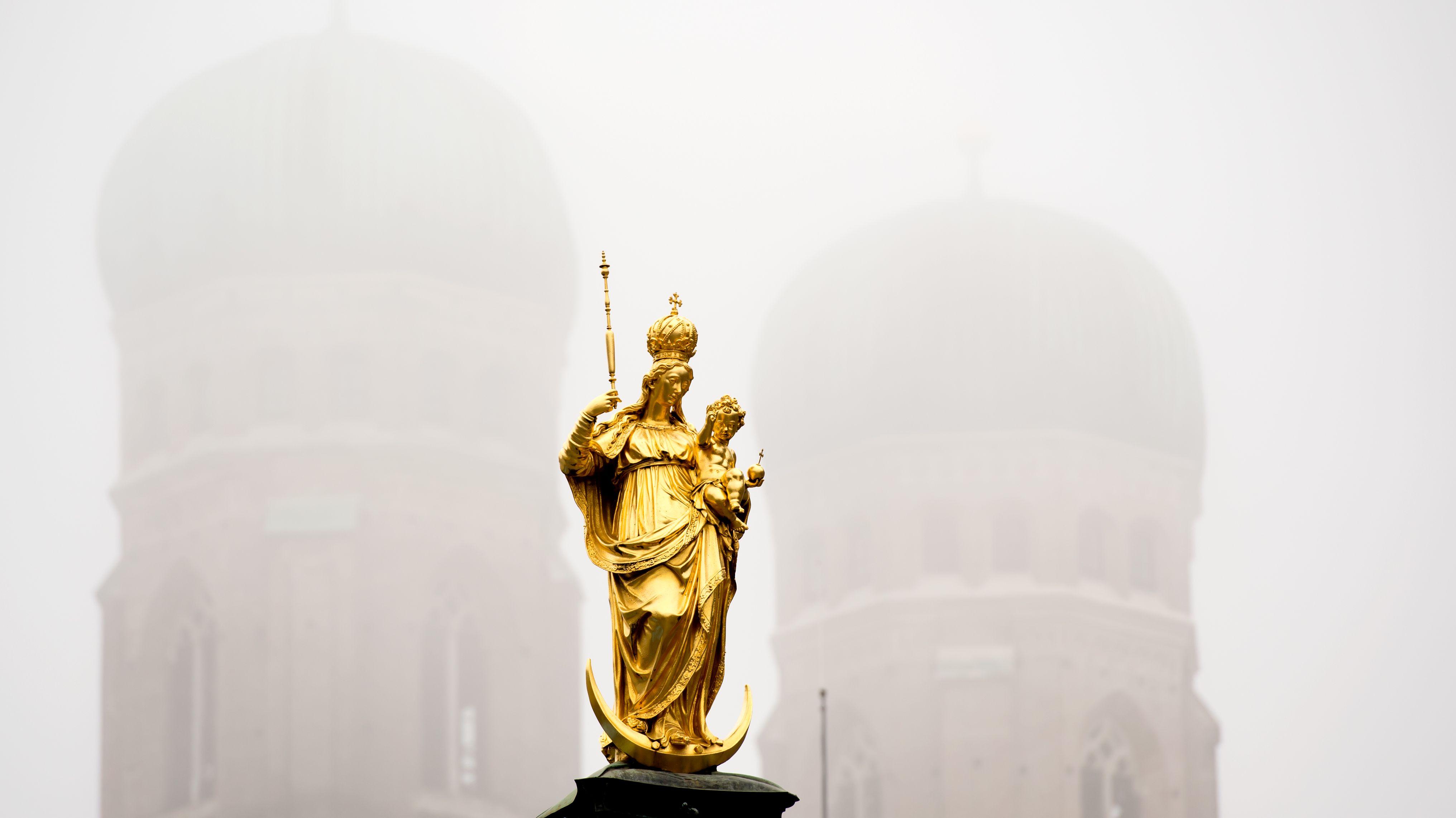 Die Mariensäule auf dem Marienplatz in München (Bayern) zeichnet sich am 07.10.2013 im Nebel vor den Türmen der Frauenkirche ab