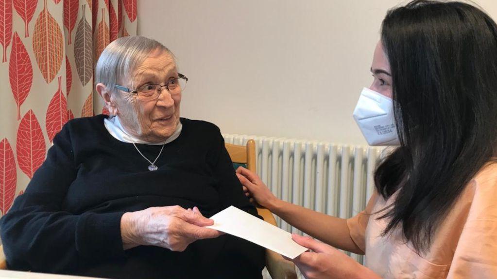 Eine junge Frau mit Maske überreicht einer Seniorin einen Brief.