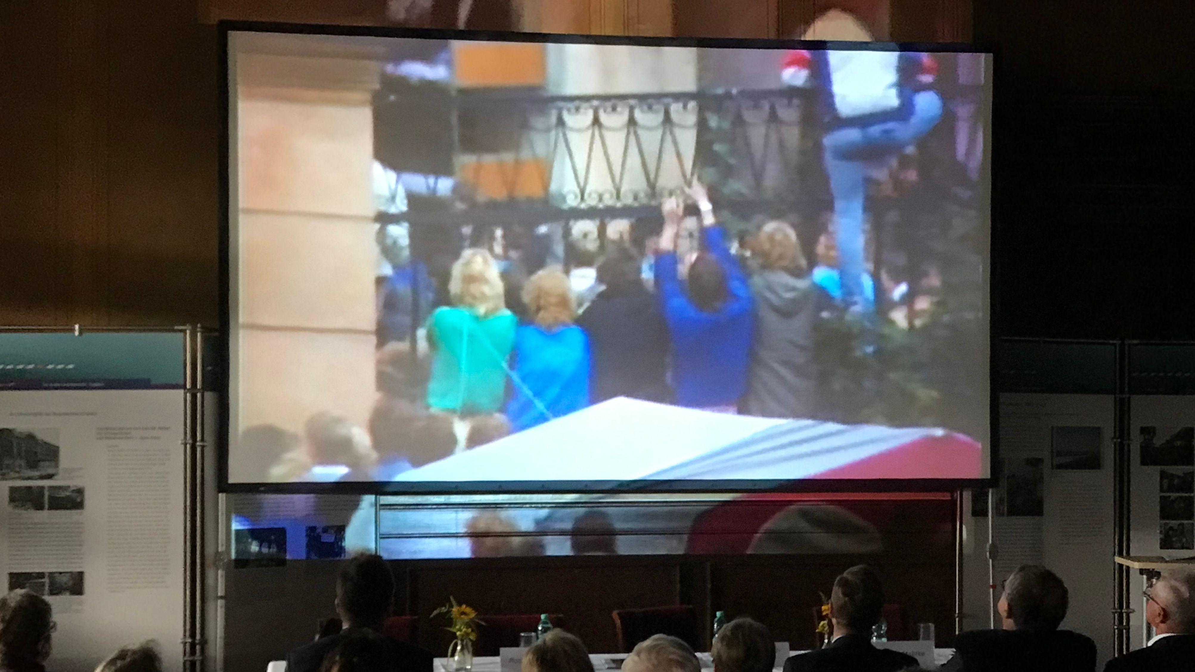 Auf einer Videoleinwand sind DDR-Bürger zu sehen, die 1989 über den Zaun in die Deutsche Botschaft in Prag steigen.
