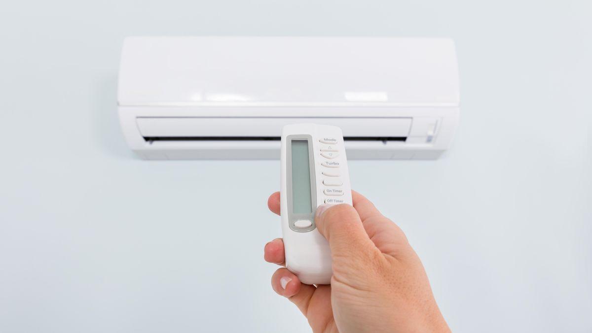 Eine Hand hält eine Fernbedienung auf eine Klimaanlage gerichtet