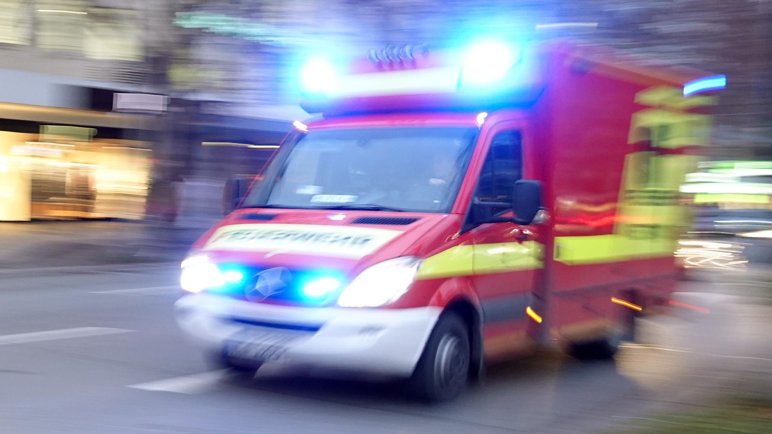 München: Ein Rettungswagen der Feuerwehr mit Blaulicht fährt eine Straße entlang (Symbolbild).