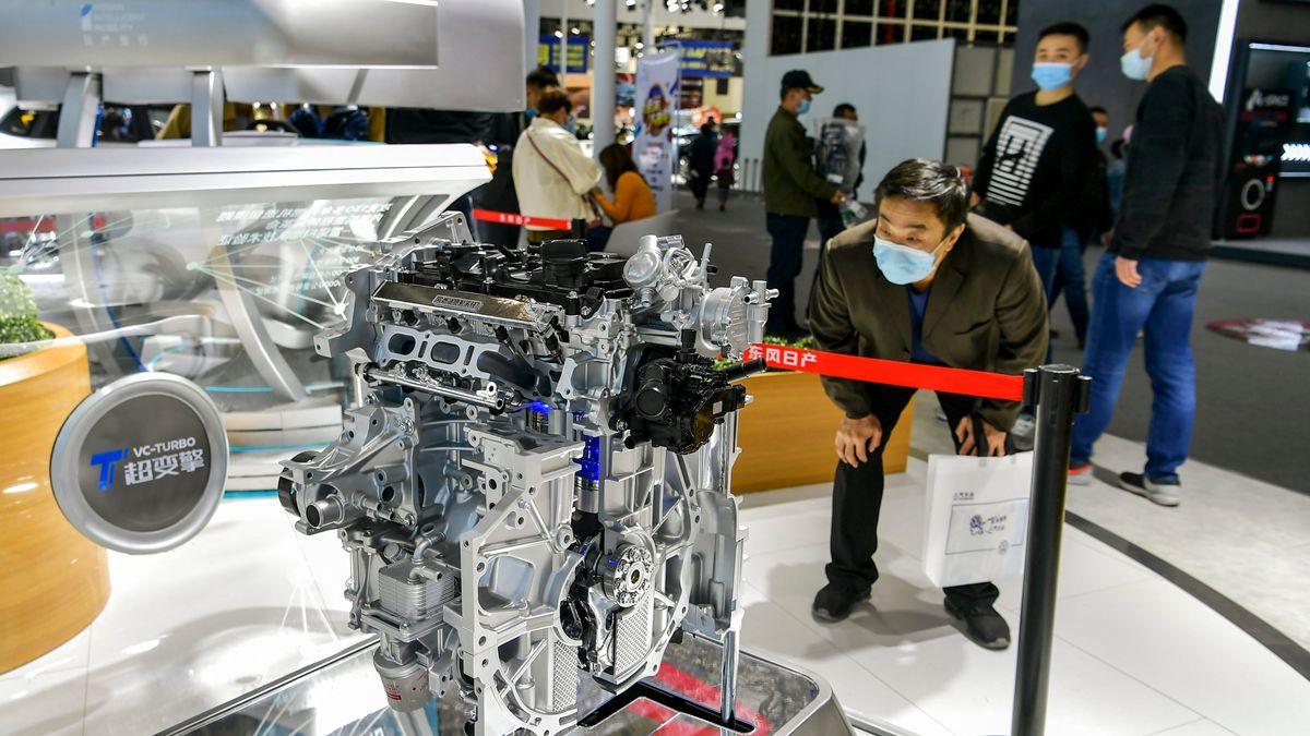 Messe-Besucher bewundert ein Motor-Modell
