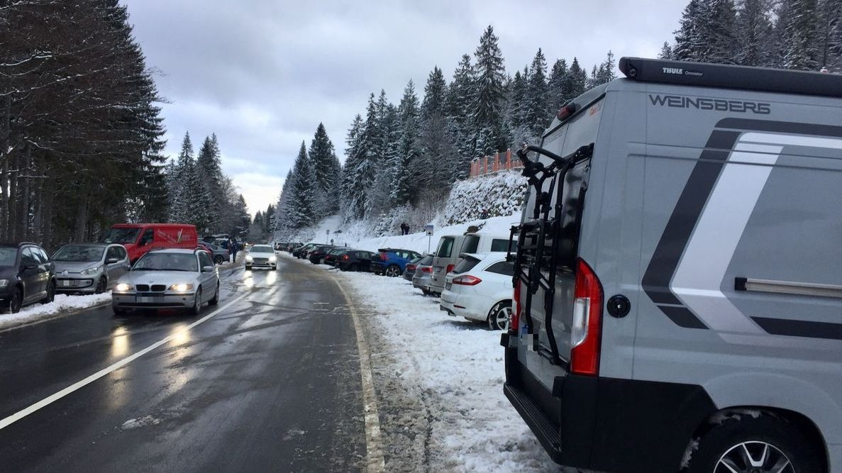 Rechts und links einer winterlich verschneiten Straße parken Autos.
