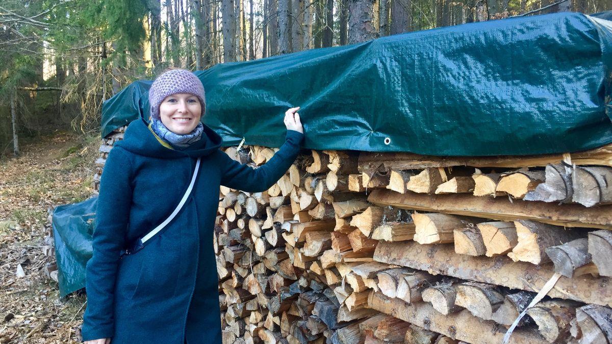 Lisa Kaml steht an einem Holzstapel in ihrem Privatwald