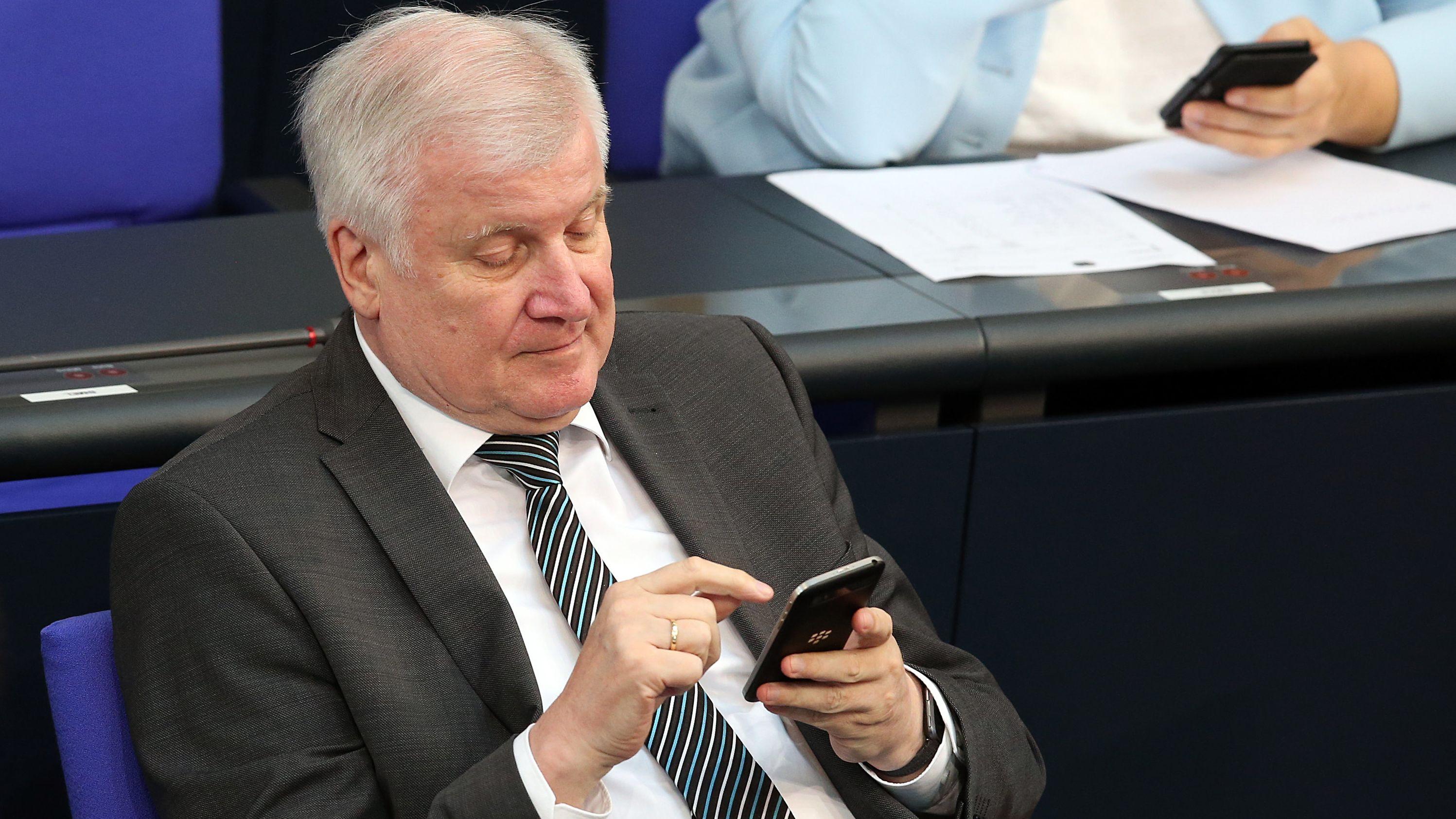 Horst Seehofer sitzt im Bundestag mit dem Smartphone in der Hand