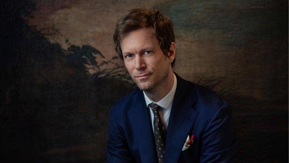 Autor Niklas Natt och Dag sitzt in einem schicken blauen Anzug vor einem Gemälde.