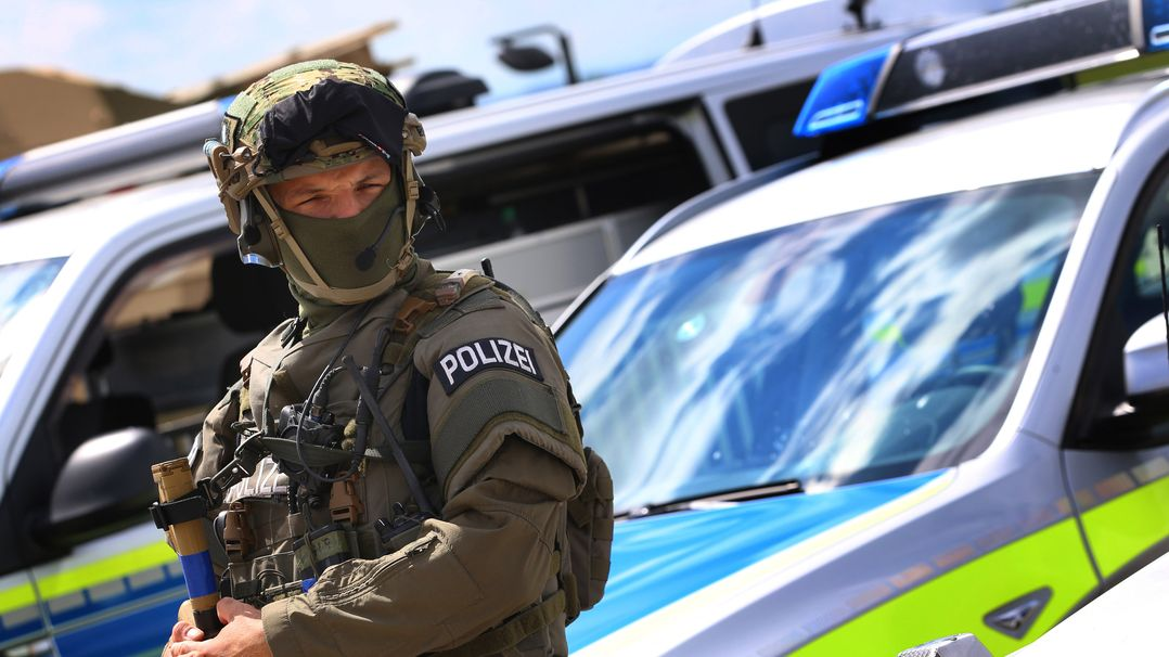 Ein Polizist des Spezialeinsatzkommandos (SEK) steht neben einem Fahrzeug (Symbolbild)