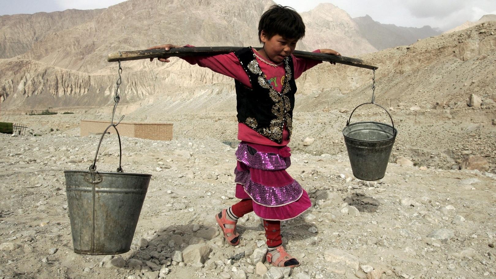 In Zentralasien trägt ein Kind zwei Eimer Wasser