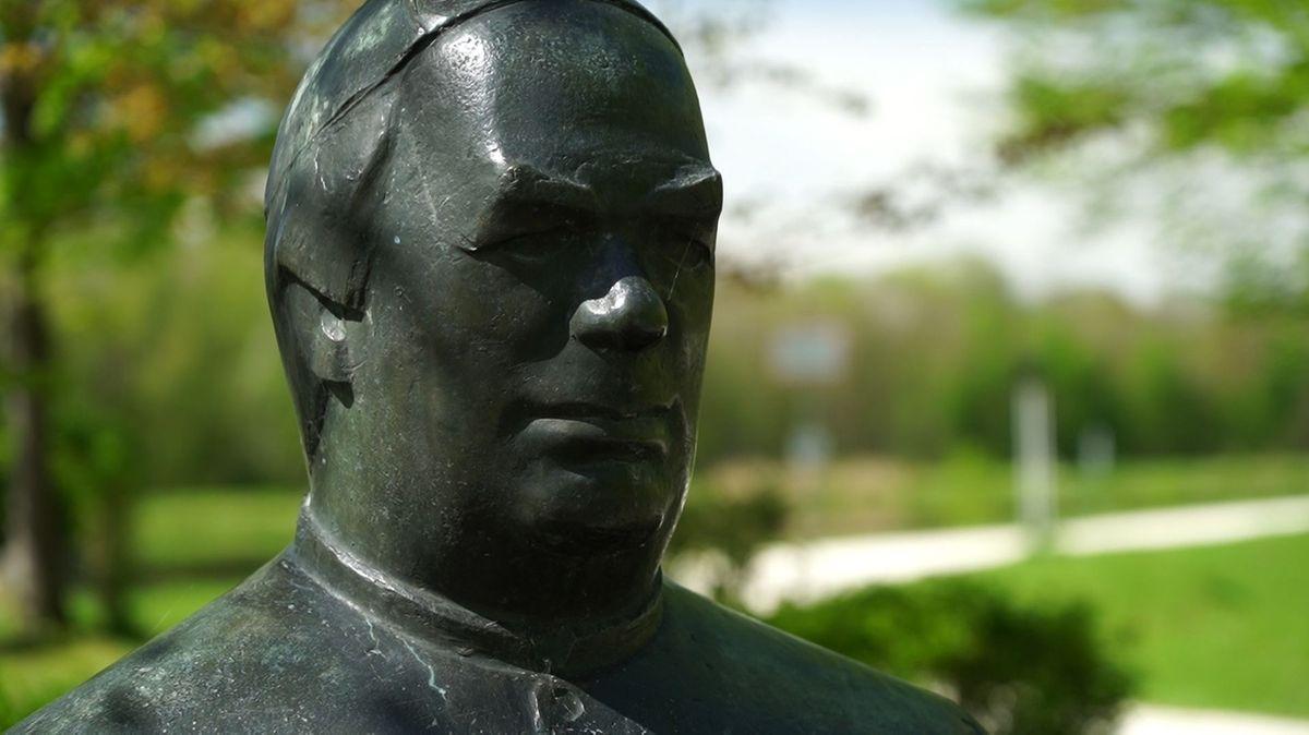 Frontaler Blick auf das Gesicht der Statue von Sebastian Kneipp in Dillingen, im Hintergrund ein Park.