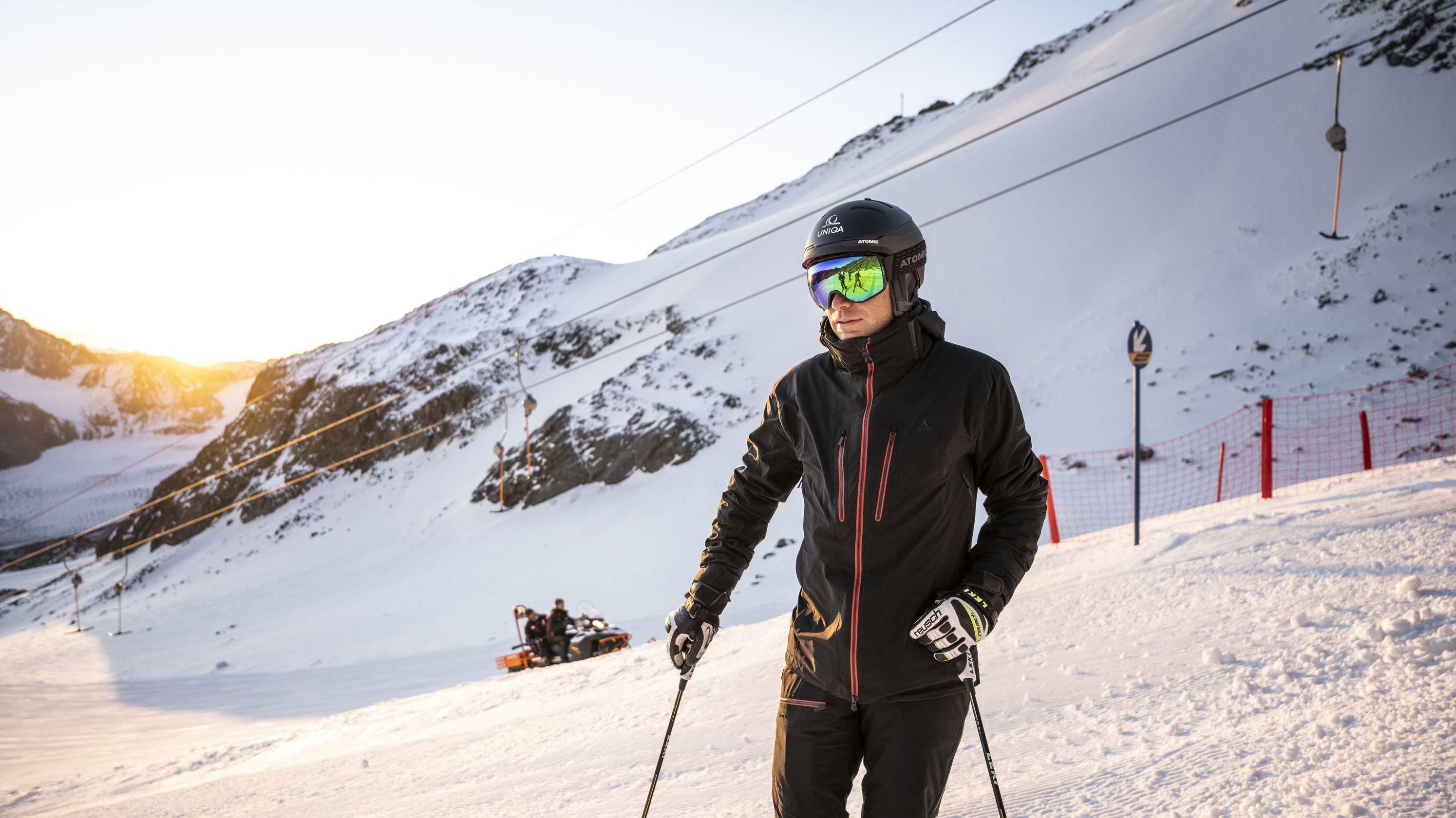 Ein Skifahrer auf einer Piste mit beheizbarer Skibekleidung, im Hintergrund ein Skilift und eine Pistenraupe.