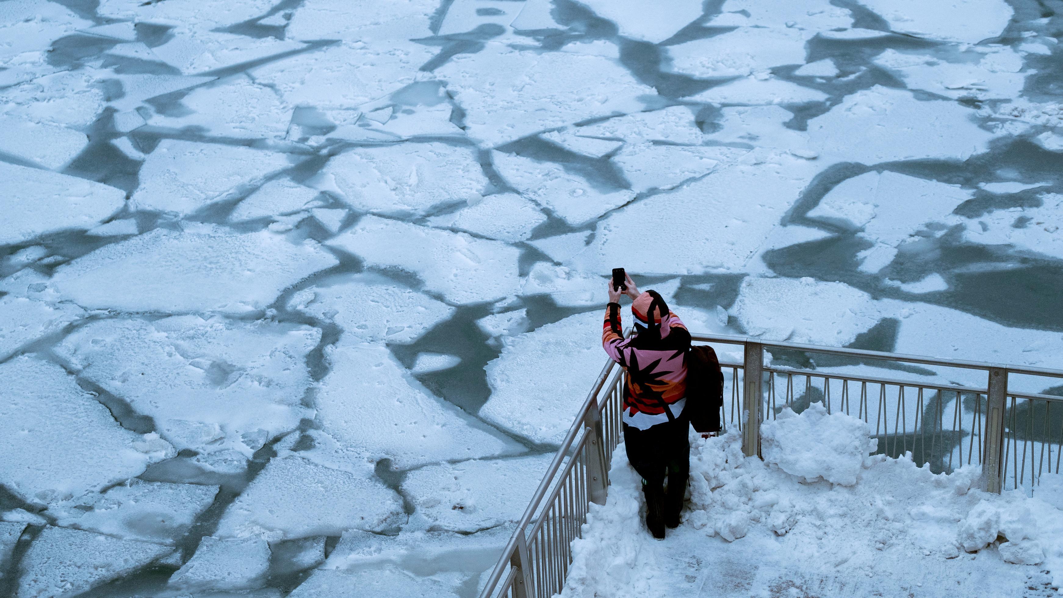 Eine Passantin fotografiert Eisschollen auf dem Chicago River