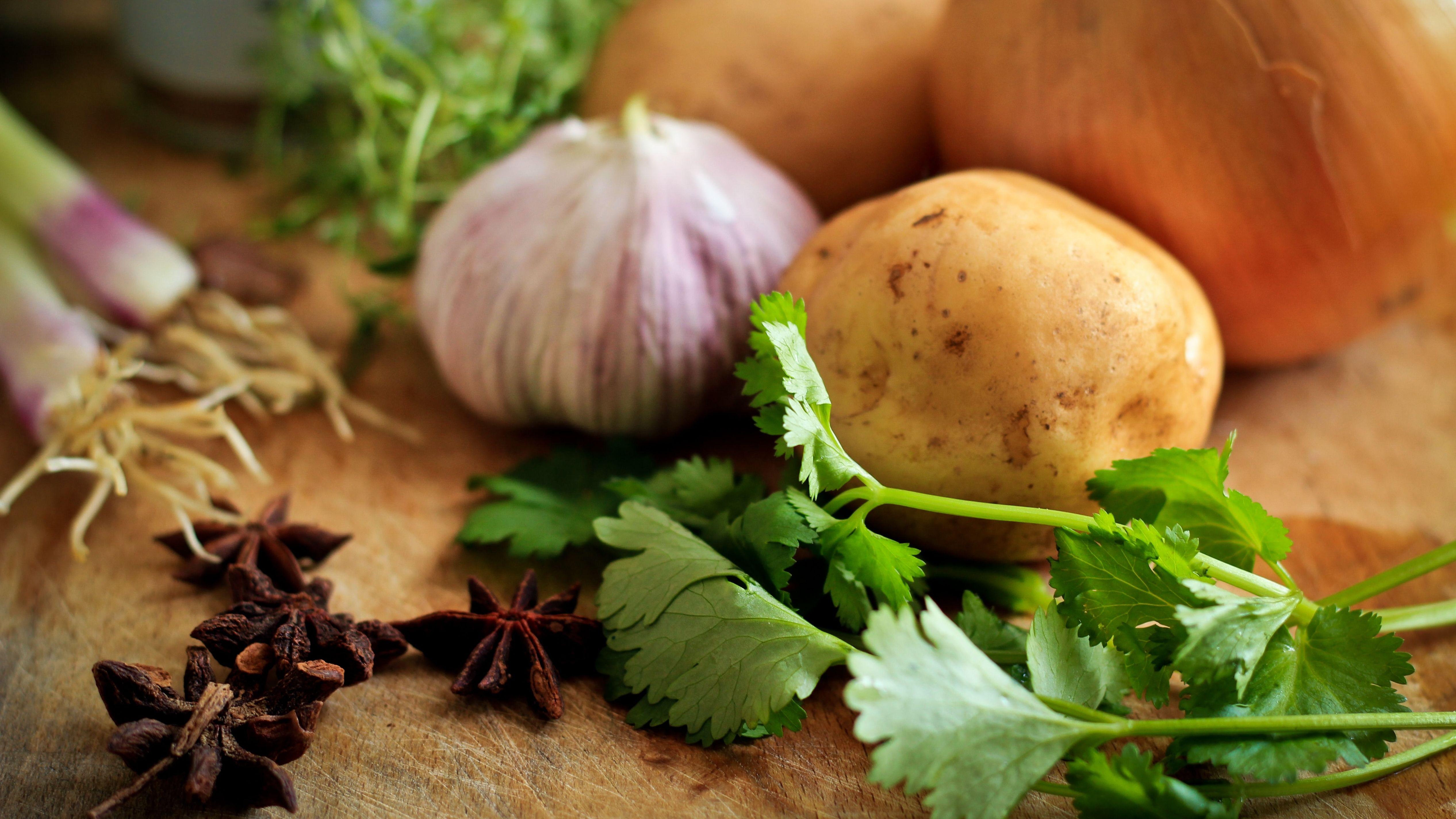 Nelken, Kartoffel, Knoblauch und Zwiebel auf einem Holzbrett