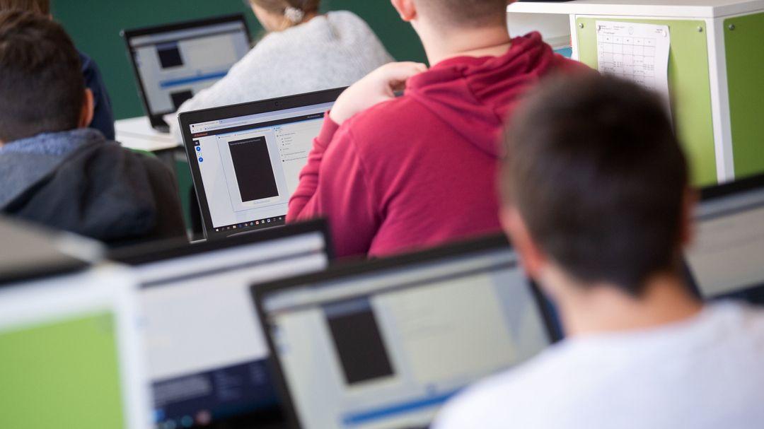 Schülerinnen und Schüler nehmen im Klassenzimmer einer neunten Klasse am Geografieunterricht mit Hilfe von Laptops und Tablets teil.