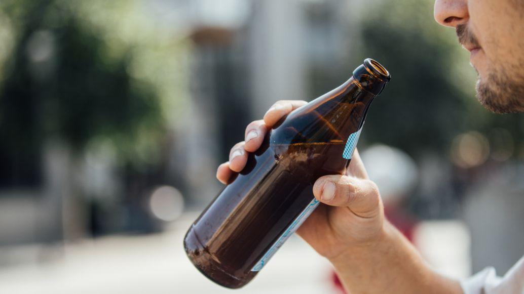 Ein Mann trinkt eine Flasche Bier.