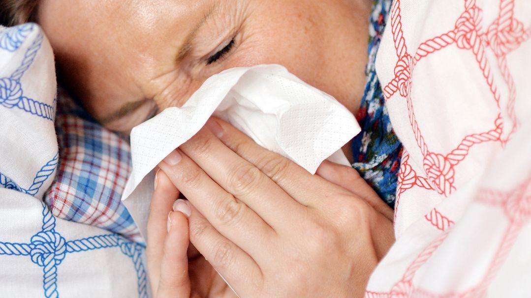 Eine erkältete Frau liegt im Bett und schneutzt sich die Nase