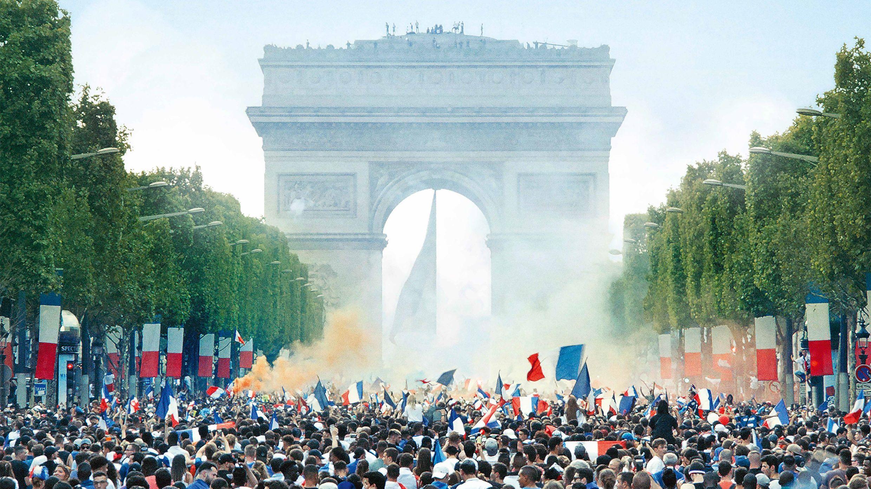 Eine Menschenmenge steht auf der Avenue des Champs-Élysées in Paris - im Hintergrund der Arc de Triomphe.