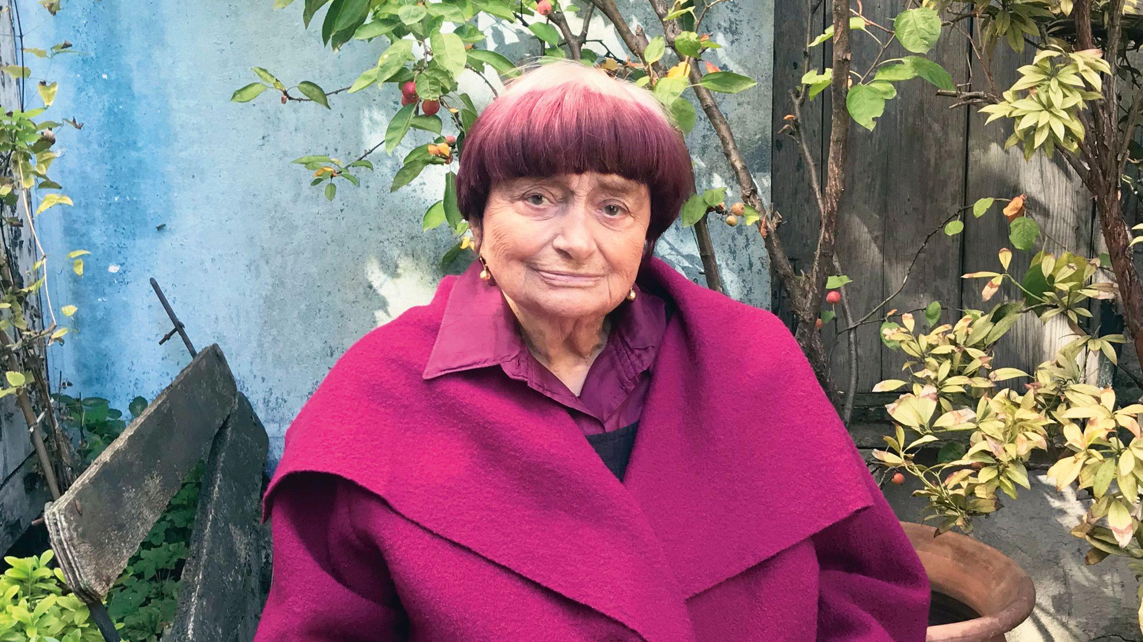 Regisseurin Agnès Varda sitzt auf einer halb verfallenen Holzbank in einem Hinterhof, sie ist in einen pinken Mantel gehüllt