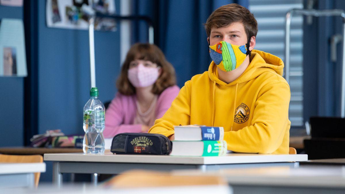 Bayern, Unterhaching: Schüler und Schülerinnen einer 12. Klasse des Lise-Meitner-Gymnasiums nehmen am Unterricht teil und tragen Mundschutze.