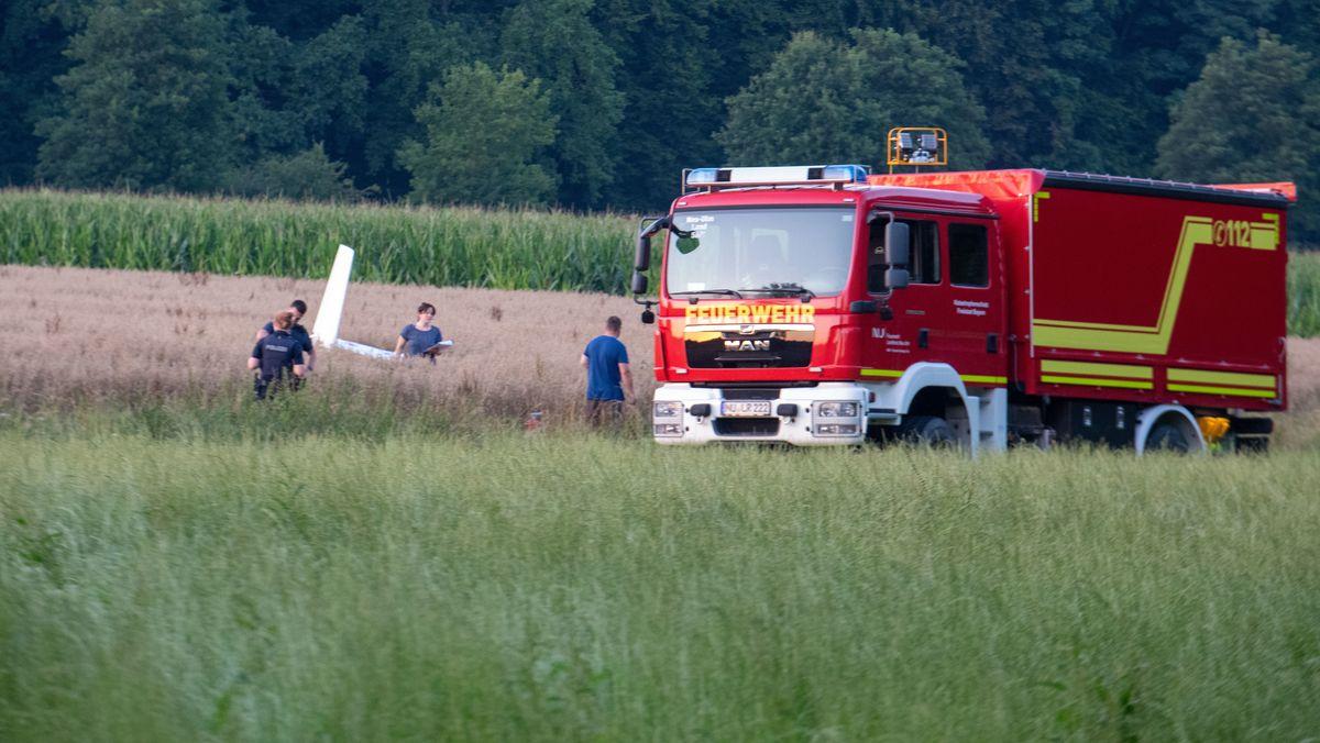 In einem Getreidefeld ist das Wrack eines Kleinflugzeuges zu sehen. Einsatzkräfte und ein Feuerwehrauto haben den Unfallort erreicht.