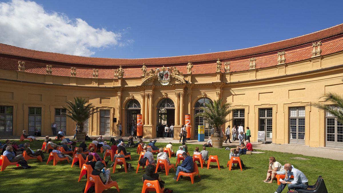 Zuhörer beim Erlanger Poetenfest sitzen auf niedriegen, orangen Plastikstühlen im Schlossgarten vor der Orangerie