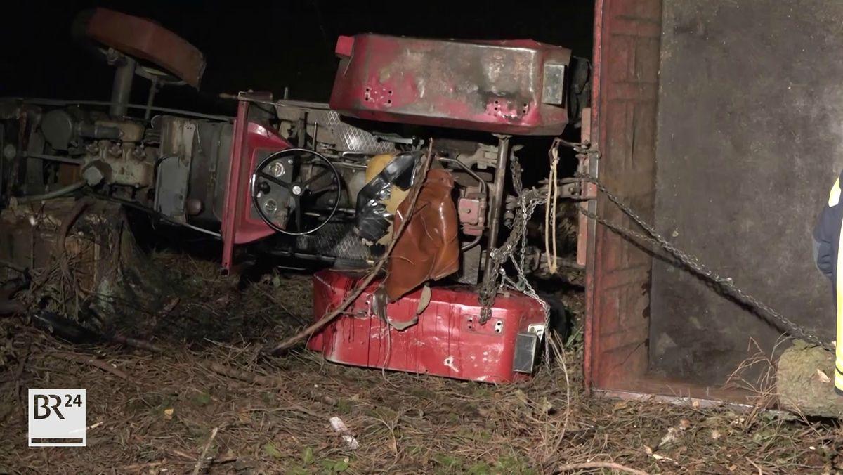 Umgekippter Traktor auf Waldboden in der Dunkelheit