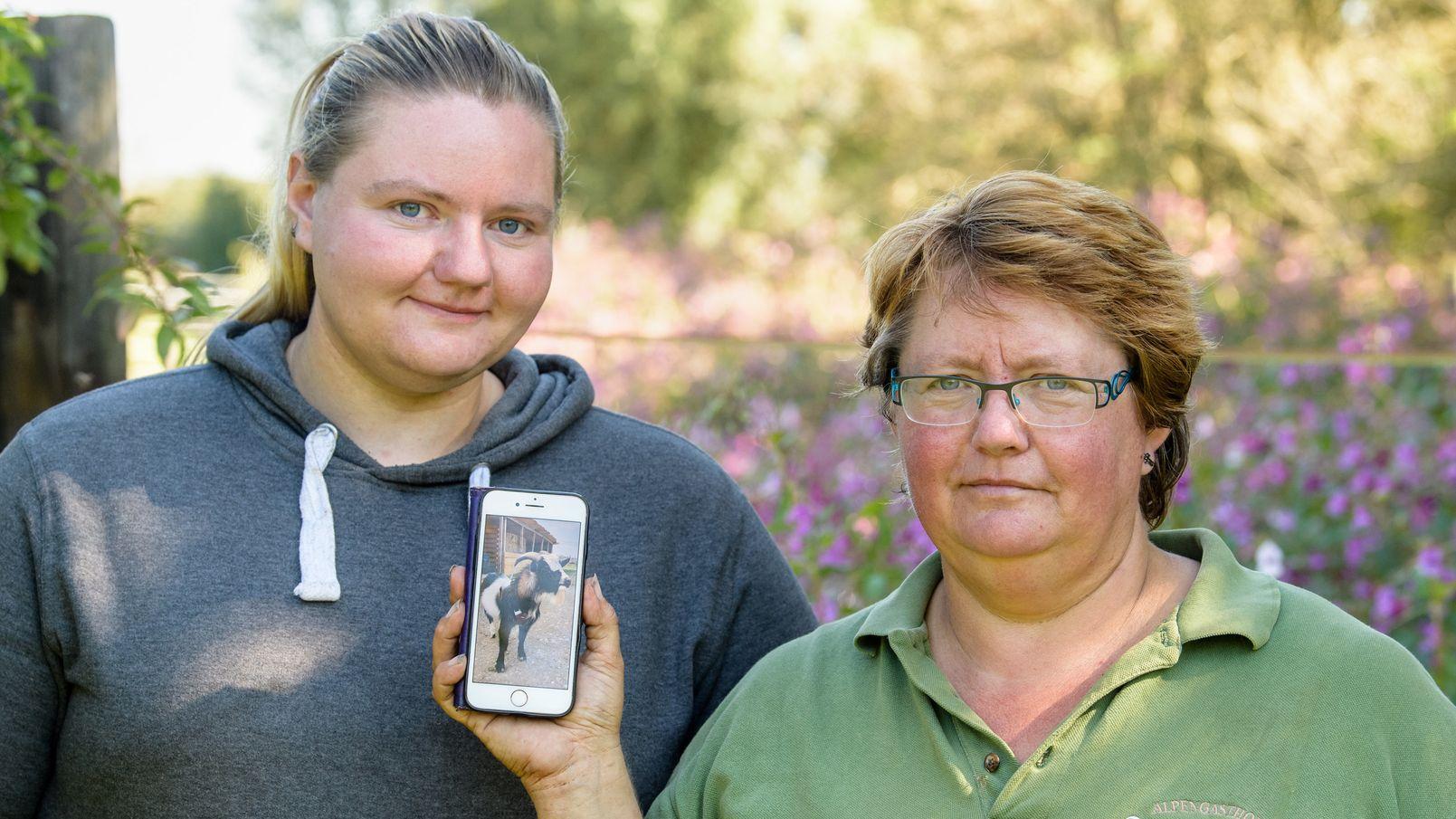 """Elisabeth A. (r) und Tochter Magdalena zeigen ein Bild vom Ziegenbock """"Hui Buh""""."""