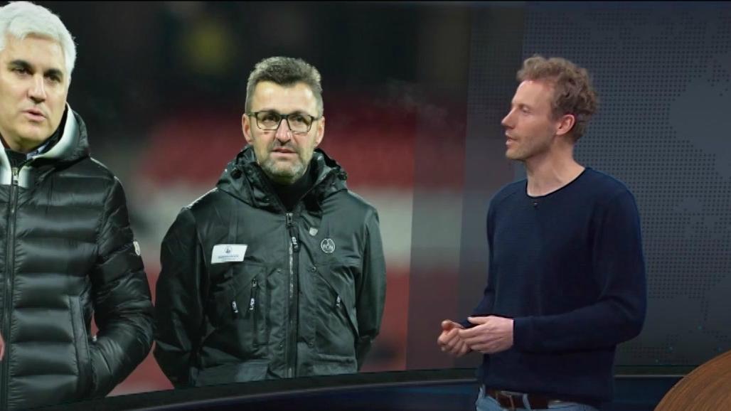 BR-Sportreporter Jan Wiecken vor einem Bild mit Andreas Bornemann und Michael Köllner