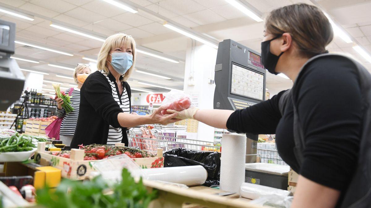 Eine Kundin wird in einem Lebensmittelgeschäft trägt eine Maske als Mund- und Nasenschutz. In Rosenheim gilt seit Mittwoch eine Maskenpflicht.
