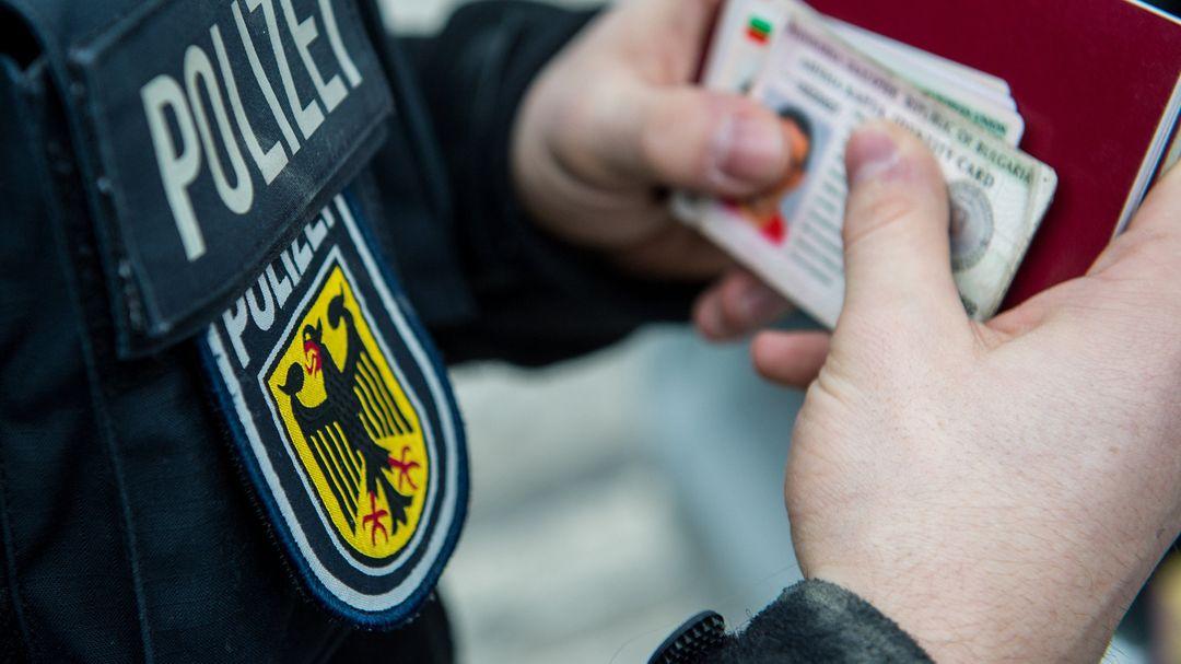 Ein Beamter der Bundespolizei hält bei einer Kontrolle mehrere ausländische Ausweise in den Händen.