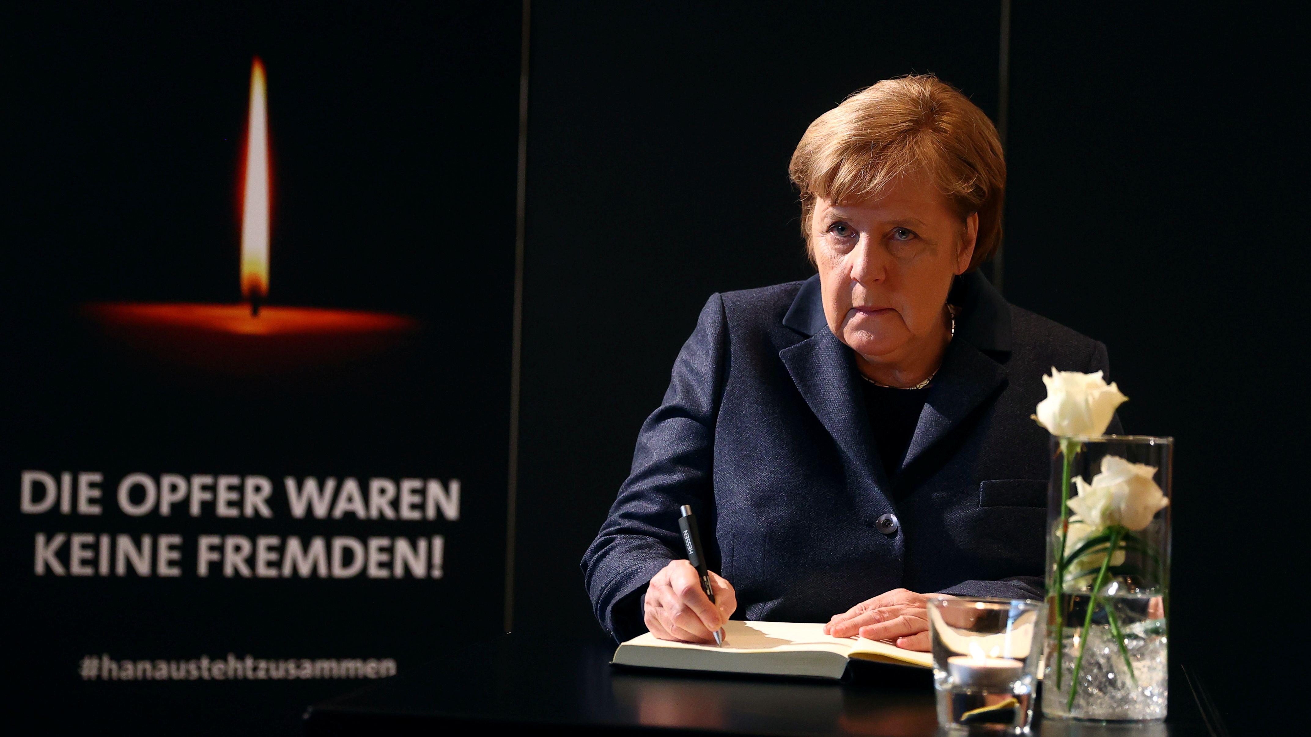 Bundeskanzlerin Angela Merkel (CDU) unterschreibt das Kondolenzbuch bei der Gedenkfeier für die Opfer des Anschlags von Hanau.