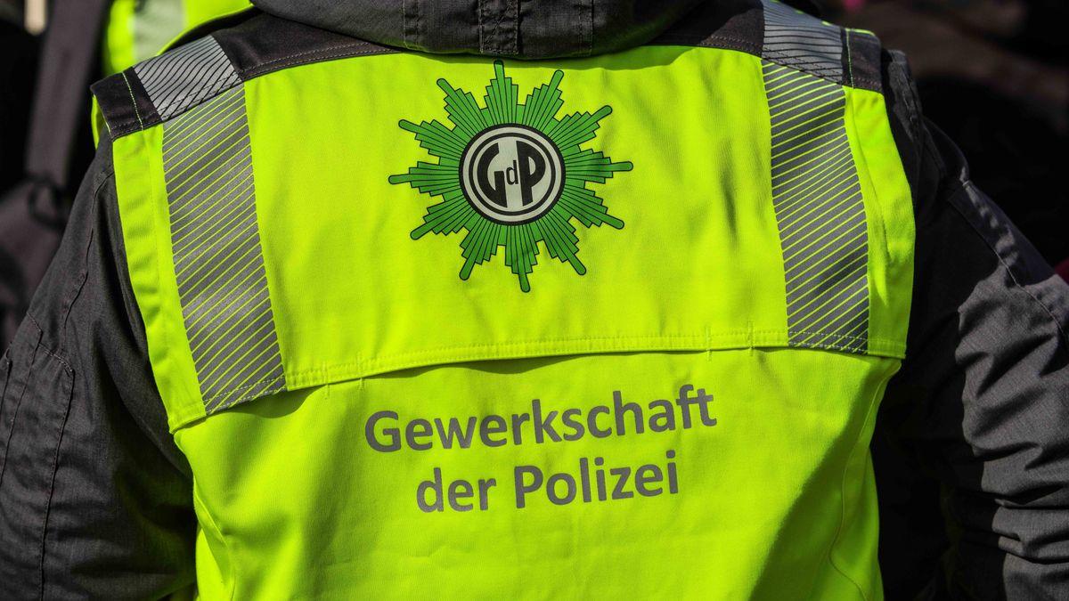 Ein Polizist trägt eine Gelbe Warnweste der Gewerkschaft der Polizei (GdP)